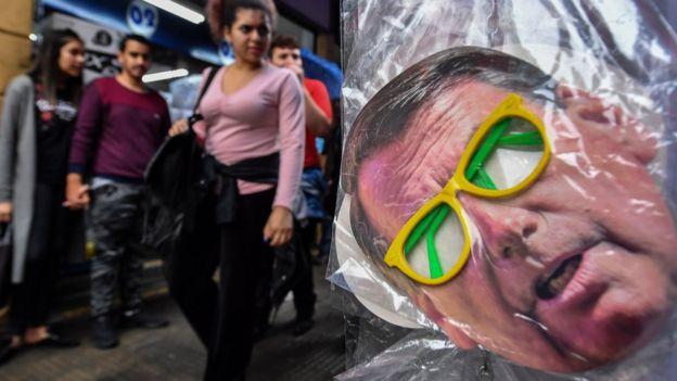 Pedestres caminham perto de máscara com rosto de Bolsonaro