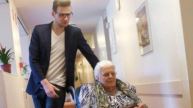 Jurrien Mentink empujando una residente en silla de ruedas
