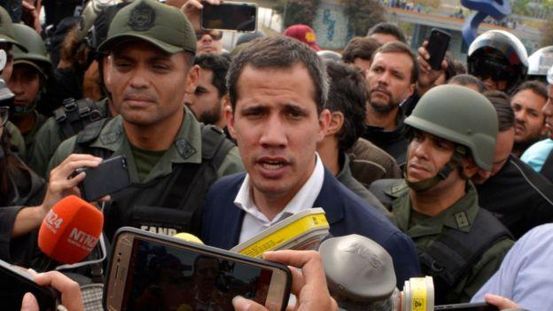 Juan Guaidó hablando rodeado de militares.