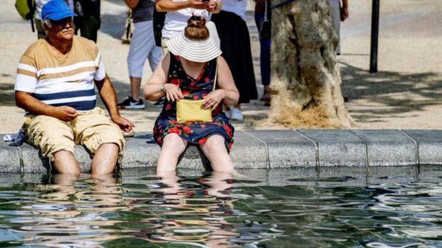 Hombre y mujer refrescándose en una fuente.