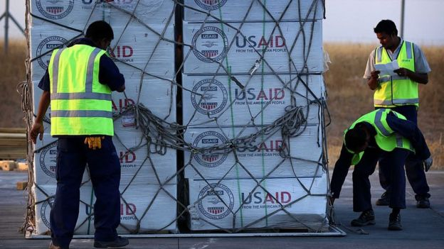 Funcionarios mueven una carga de la USAID en un aeropuerto.