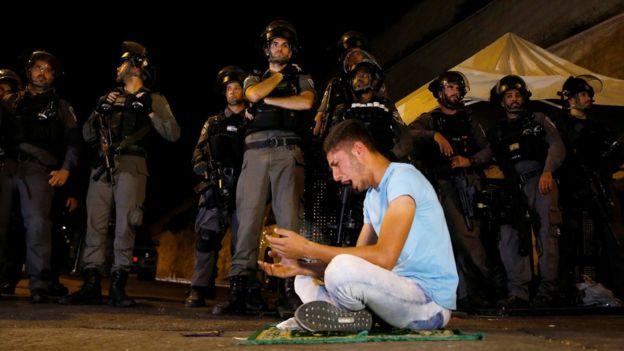 Palestino orando en la calle frente a soldados
