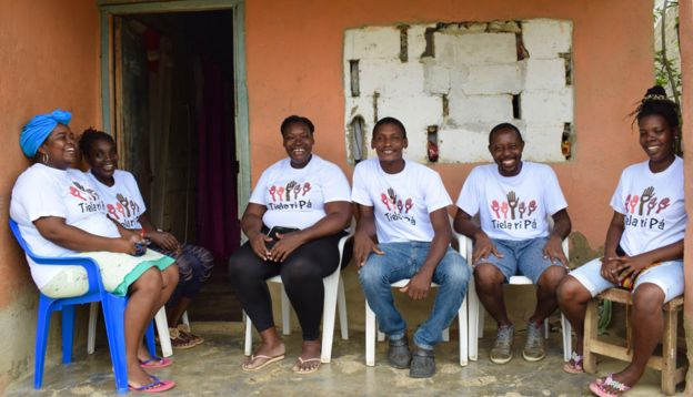 Volunteers for Tiela Ri Pá sit on the porch of a house in Palenque