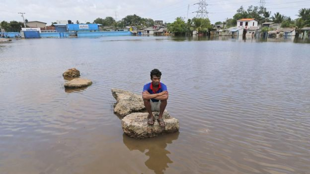 A Sri Lankan sits on a concrete slab in a flood affected area Colombo, Sri Lanka, Sunday, May 22, 2016