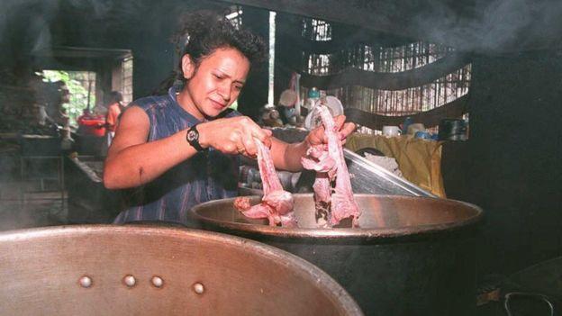 Foto de una mujer en San Salvador cocina iguanas