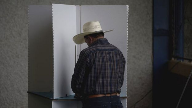 A Guatemalan man wearing a cowboy hat casts his cote in the August 2019 election