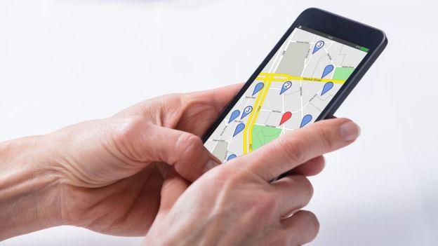 Una persona con el teléfono en la mano y un GPS