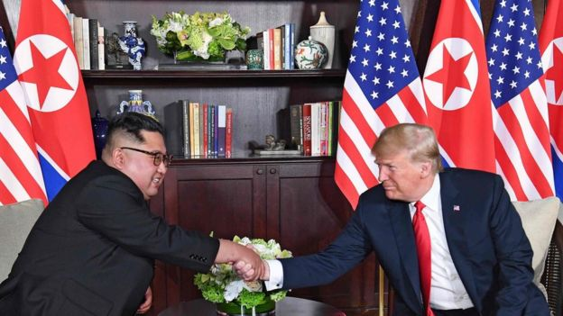 "US President Donald Trump (R) shakes hands with North Korea""s leader Kim Jong-un (L) as they sit down for their historic US-North Korea summit"
