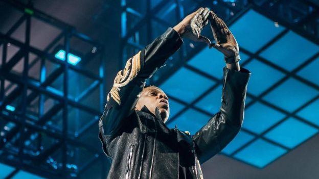 Jay Z haciendo el símbolo del triángulo con las manos