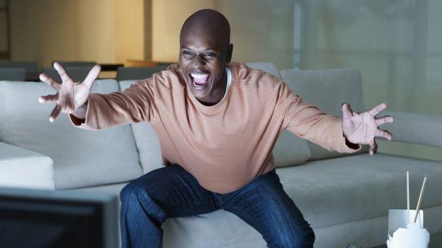 hombre mostrando euforia frente al televisor