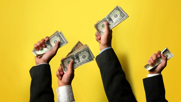Manos sosteniendo dólares