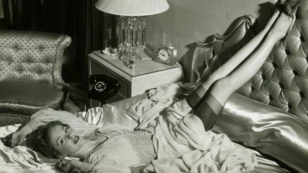 Chica en cama con medias de nylon