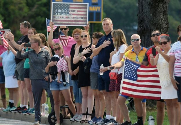 Spectators watch a hearse containing the body of the late Senator John McCain arrive for a private memorial service at the US Naval Academy in Annapolis