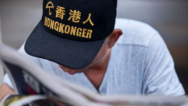 A protester and Umbrella Movement supporter reads the newspaper at the Legco complex in Hong Kong on 21 June
