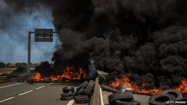Ferry workers burn tyres on both lanes of a road leading to the port of Calais on 31 July 2015