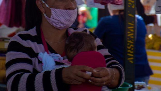 Mulher com criança em feira de SP