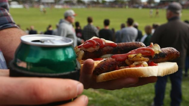 A spectator holds a beer and barbecued sausages at an Australian Rules football match in Melbourne
