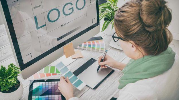 Mujer diseñando frente a una computadora.