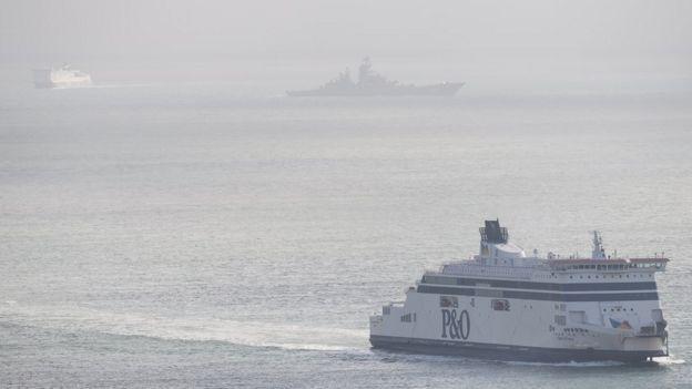 A passenger ferry passes the Russian aircraft carrier