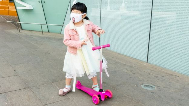 Niña china con mascarilla en un scooter