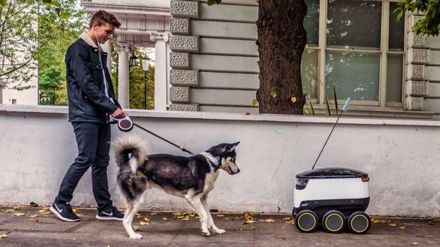 شخص يسير بكلبه إلى جانب الروبوت