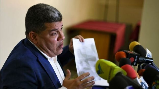 Luis Parra holds up a paper during a news conference