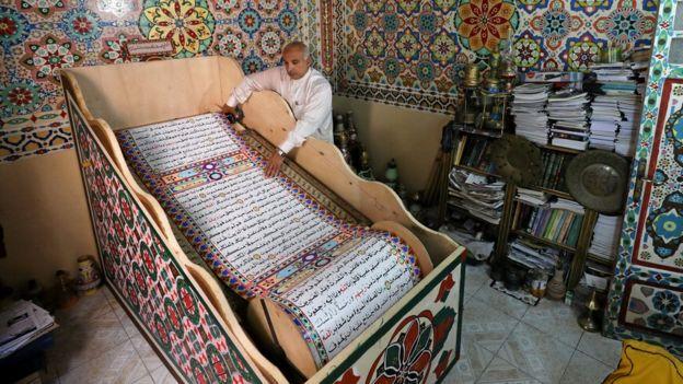 سعد محمد يسحب لفافة المصحف الذي صنعه في بلدة بلقينا شمال القاهرة
