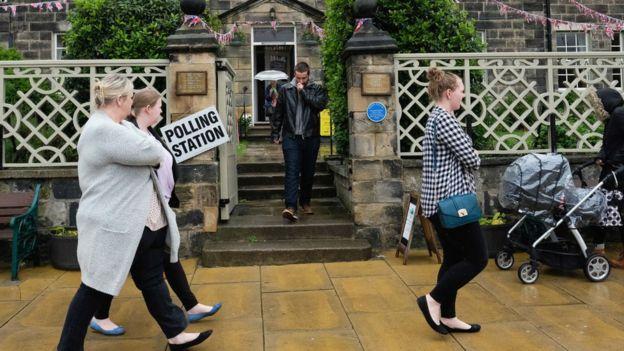 Personas caminan frente a un centro de votación en Reino Unido.