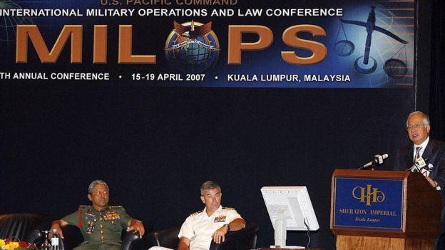 Ông Raul Pedrozo (ngồi giữa) trong sự kiện An ninh hàng hải quốc tế tại Malaysia 2007 với tư cách là Cố vấn luật của Bộ Tư lệnh Thái Bình Dương Mỹ. Bên phải ông là Tham mưu trưởng quân đội Malaysia Abdul Aziz Zainal, bên trái ông Phó Thủ tướng Malaysia Najib Razak đang phát biểu.