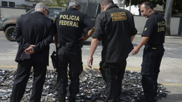 Agentes da Polícia Federal observam armas