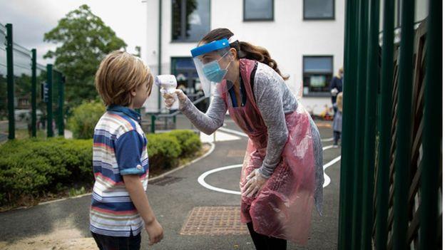 У ребенка измеряют температуру на входе в школу в Лондоне