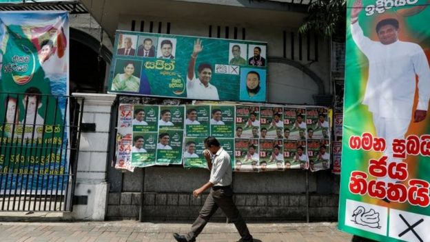 """A man walks past the posters of Sajith Premadasa, Sri Lanka""""s presidential candidate of the New Democratic Front alliance, in Colombo, Sri Lanka"""