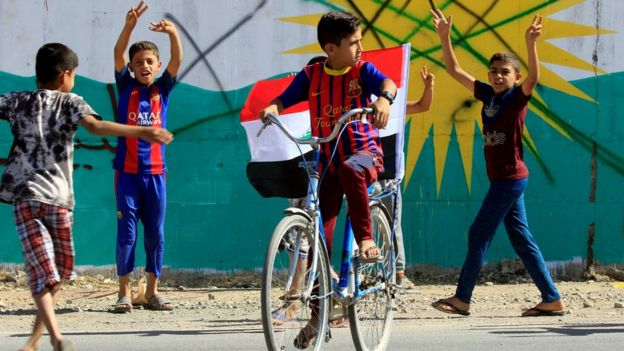 A boy drives a bicycle with an Iraqi flag in Dibis area on the outskirts of Kirkuk