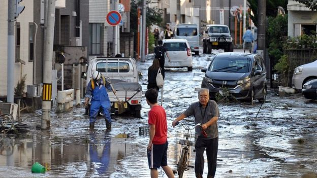 People walk in a street covered with mud in Kawasaki, near Tokyo, Japan, 13 October 2019