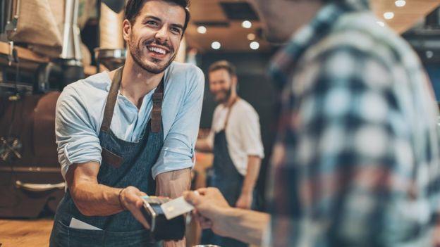 Imagem mostra vendedor sorrindo enquanto recebe pagamento de cliente com cartão de crédito