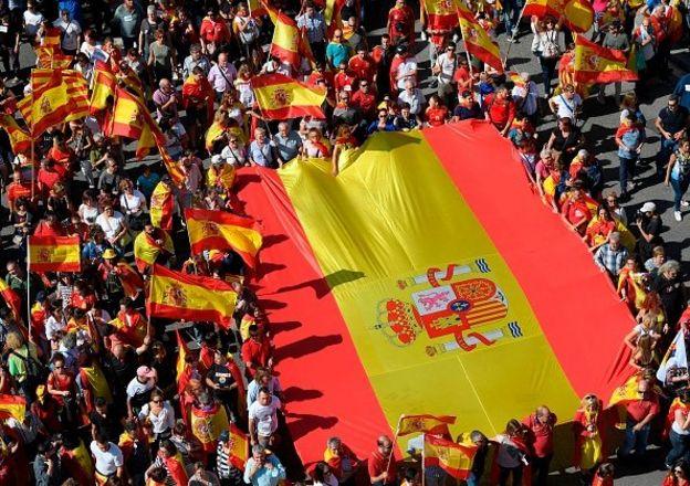 ผู้ประท้วงถือธงสเปนขนาดใหญ่ในการเดินขบวนเพื่อสนับสนุนการเอกภาพของสเปนเมื่อวันที่ 8 ตุลาคมที่ผ่านมา