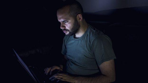 Homem mexendo no computador à noite
