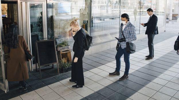Gente con distancia social en la entrada de una tienda.