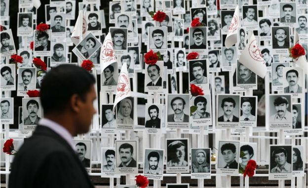 A man looks at photos of people executed in Iran during a rally outside the United Nations headquarters in New York on Tuesday, 20 September, 2016.