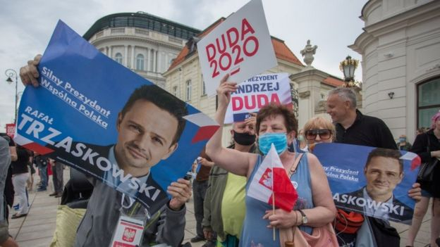 Supporters of President Andrzej Duda and his rival Warsaw mayor Rafal Trzaskowski hold placards during a presidential election campaign event in Warsaw, Poland, June 26, 2020