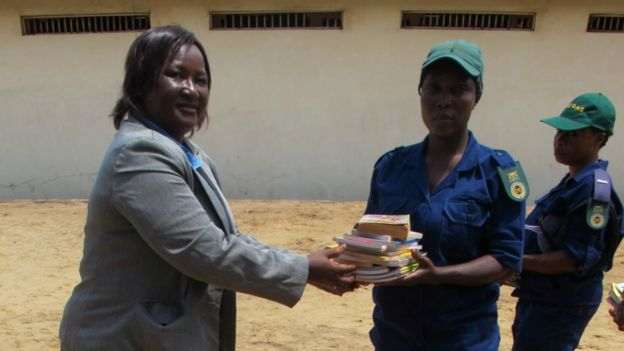 Woman hands books to prison guard