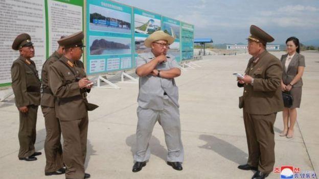 Kim Jong-un chuyện trò với các quan chức nhà máy ướp cá trong khi Đệ nhất Phu nhân Ri Sol-ju đứng nhìn