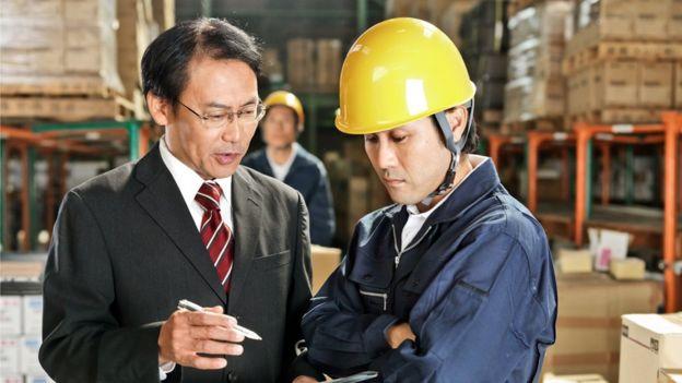 Trabalhadores japoneses conversam em depósito