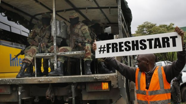 man holding a sign reading #freshstart, next to a vehicle full of soldiers