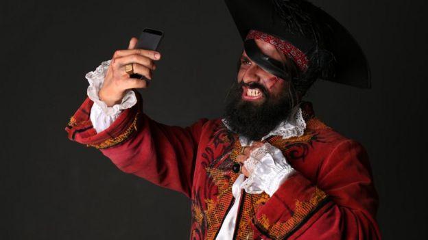 Un hombre disfrazado de pirata se mira en un teléfono.