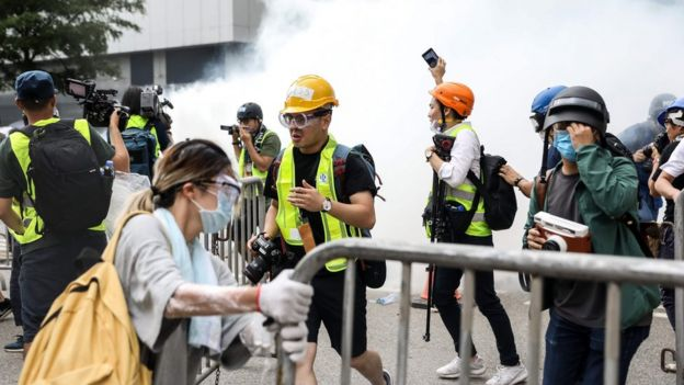 Protesters and members of the media react after police fired tear gas during a rally against a controversial extradition law proposal outside the government headquarters in Hong Kong on June 12, 2019.