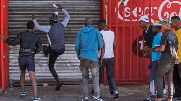 Des pillards qui essaient d'entrer par effraction dans un magasin
