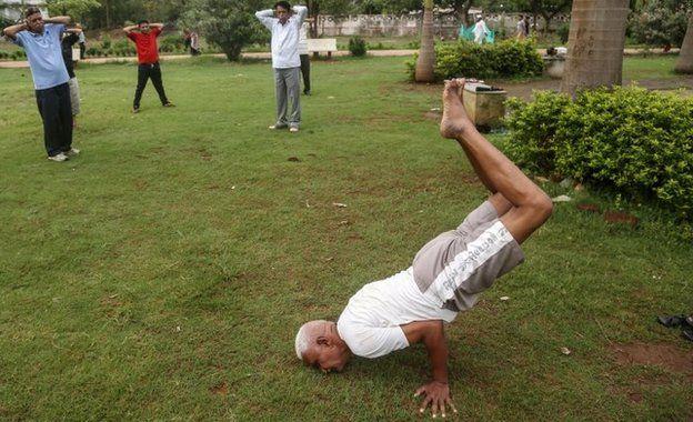 Indian men practice Yoga at a Jogger's park in Mumbai, India, 16 June 2015.