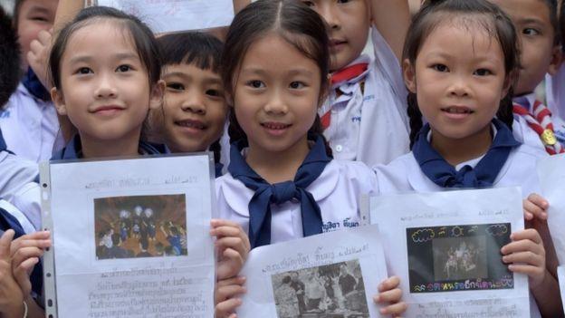 أطفال تايلانديون يحملون صورة أقرانهم الذين تم إنقاذهم