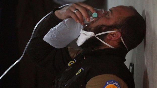 A rescue worker breathes through an oxygen mask after helping people following a suspected chemical attack in Khan Sheikhoun, Idlib province, Syria (4 April 2017)